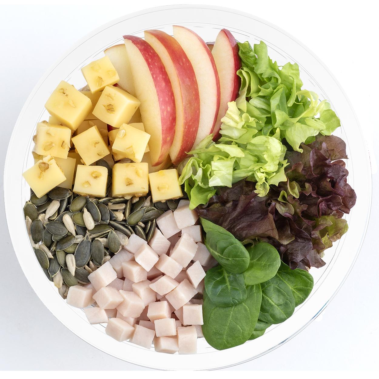 Ensalada completa con manzana, pavo, escarola lisa, espinaca, brote lollo rojo, pipas de calabaza, semillas de girasol, queso con nueces y vinagreta de albahaca y semillas de amapola