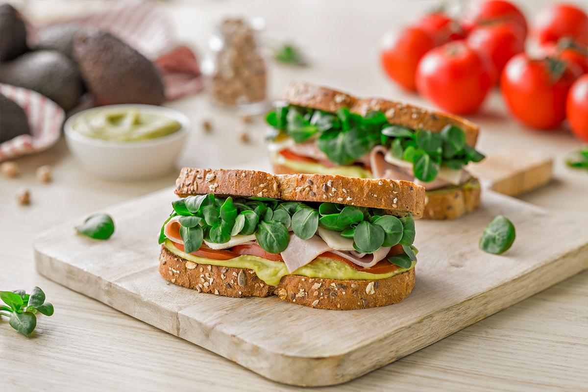 Sandwich vegetal con hummus de aguacate, canonigos, tomate, jamon cocido en lonchas y queso tiernos en lonchas
